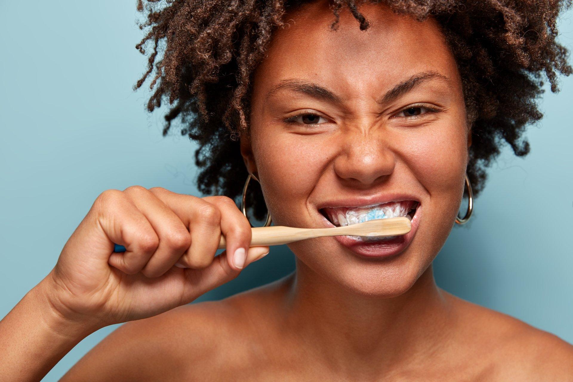 Woman of Mixed Race Brushing Teeth